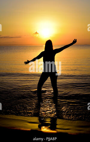 Yoga poses a tree in the sea at sunrise. - Stock Photo