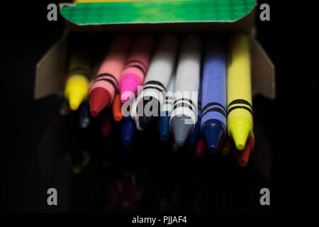 Crayons spilling out of a box. Kids coloring tools. Various colors of children's wax sticks for drawing. - Stock Photo