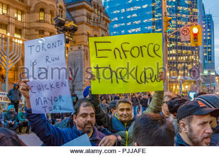 Toronto taxi drivers protest against Uber X. They claim the city is not enforcing its bylaws. For hours, they blocked the intersection of Queen St. We - Stock Photo