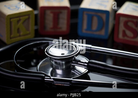 Child care and sick kids hospital concept. KIDS spelled in block text with stethoscope  on a black background. - Stock Photo