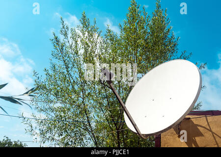 Satellite dish on the wall of a country house - Stock Photo
