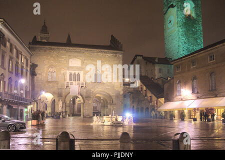 Italy, the old town of Bergamo.  The Piazza Vecchia  is lit up on a rainy winters evening - Stock Photo