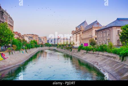 sunset cityscape in Bucharest, Romania. Dambovita river and Justice palace - Stock Photo