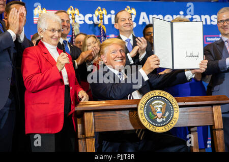 President Donald J. Trump is applauded as he displays his signature after signing the Executive Order on Strengthening Retirement Security in America on Friday, August 31, 2018, at the Harris Conference Center in Charlotte, North Carolina.  People:  President Donald Trump - Stock Photo