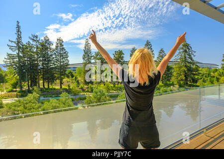 Cupertino, CA, United States - August 12, 2018: tourist woman enjoy the view of Apple Park with futuristic Campus from Roof Terrace of Apple Park Visitor Center in Silicon Valley, California. - Stock Photo