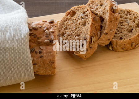 Sliced multi seeded baguette on a bread board. - Stock Photo