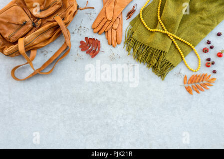 Autumn fashion flat lay in orange and green tones, on gray concrete background, with copy space. - Stock Photo
