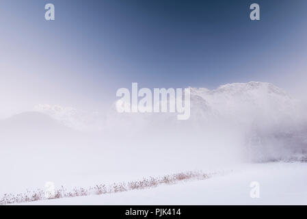 Misty mood in front of the wintry Karwendel on the frozen and snowy Schmalensee - Stock Photo