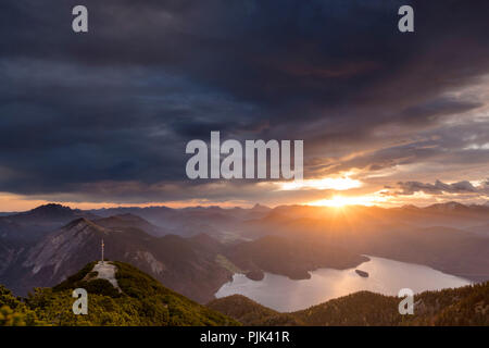 Sunrise over the Walchensee with summit cross from the Herzogstand - Stock Photo