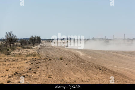 Car leaving dust cloud on a road in Namibia - Stock Photo