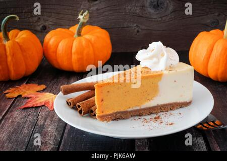 Slice of pumpkin cheesecake with whipped cream on a dark rustic wood background - Stock Photo