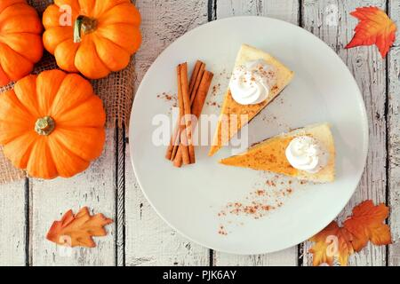 Plate with two slices of pumpkin cheesecake with whipped cream, overhead view on a white wood background - Stock Photo