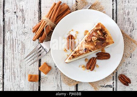 Slice of pecan caramel cheesecake, top view on a rustic white wood background - Stock Photo