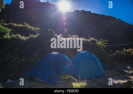 two blue tents against the layers of the morning mountains Trekking through the mountains of Canta - Peru - Stock Photo