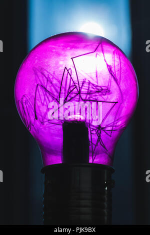 Decorative purple tungsten lamp, close-up vertical photo with selective focus and shallow DOF - Stock Photo