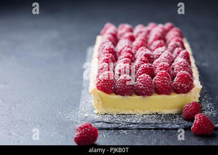 Raspberry tart with vanilla custard and white chocolate on slate board. Copy space - Stock Photo