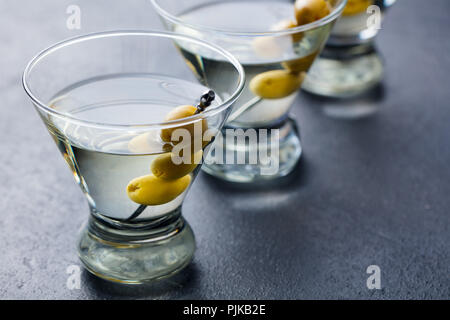 Martini cocktail with green olives. Slate background. Close up - Stock Photo