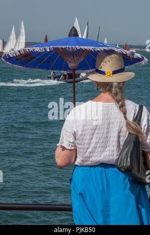 middle aged lady or woman holding a blue paraso; to provide shade from the sun on a sunny day at cowes week at cowes on the isle of wight. - Stock Photo