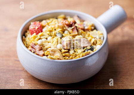 Granola, muesli in ceramic bowl. Healthy breakfast. Organic oats with apples, berries and nuts - Stock Photo
