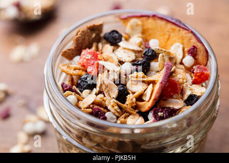 Granola, muesli in glass jar. Healthy breakfast. Organic oats with apples, berries and nuts - Stock Photo