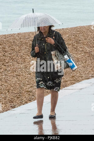 older or middle aged woman walking along a seaside pathway in the rain with an umbrella to protect against the wet weather and downpour. - Stock Photo