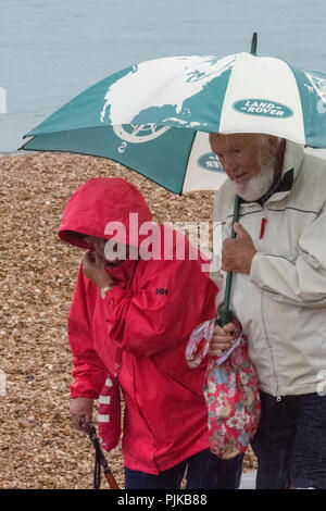 an older or elderly couple walking along a beach in the rain holding a large umbrella to protect against the wet and rainy weather. - Stock Photo