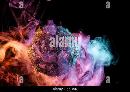 Close up  of a silver shiny decoration Christmas balls in colored purple-red smoke, on an isolated black background. Concept of a modern Christmas car - Stock Photo
