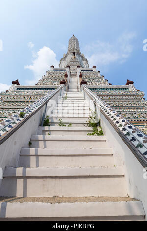 Front and low angle view of decorated Wat Arun temple in Bangkok, Thailand, on a sunny day. - Stock Photo