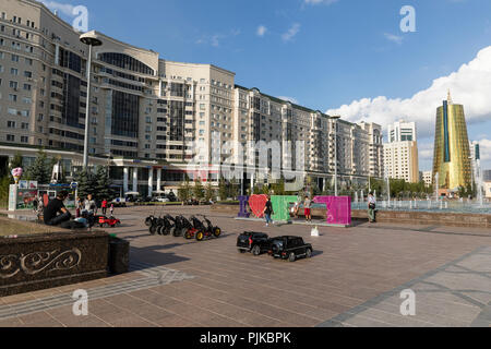 Astana, Kazakhstan, August 2 2018: Pedestrian zone with park and golden towers in the center of Astana, Kazakhstan - Stock Photo