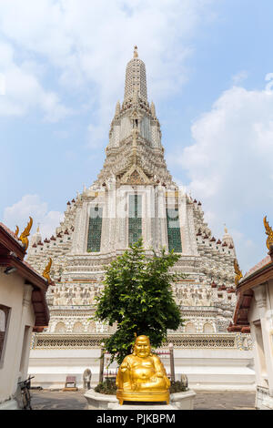 Golden statue of sitting Buddha and decorated Wat Arun temple viewed from the front in Bangkok, Thailand, on a sunny day. - Stock Photo