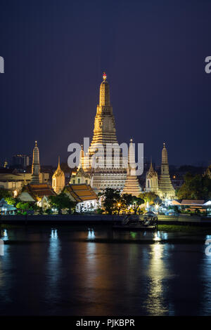 Beautiful view of lit Wat Arun temple next to Chao Phraya River in Bangkok, Thailand, in the evening. - Stock Photo