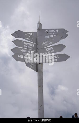 Metal pillar Pointer on top of mount Tahtali in Turkey showing the distance to different cities of the world - Stock Photo