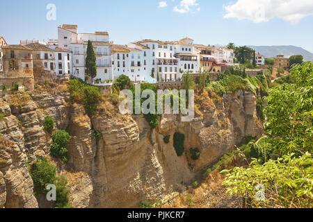 White spanish homes on a sunny day in spain, on top of a rockface on the edge of a deep canyon - Stock Photo