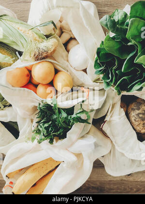 zero waste shopping concept. fresh vegetables in eco cotton bags on table in the kitchen. lettuce, corn, potatoes, apricots, bananas, rucola, mushroom - Stock Photo