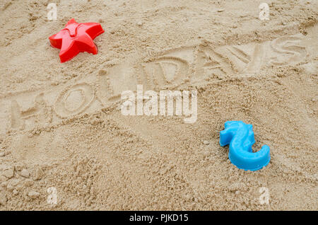 Word holiday written in sand. Concept of summer holidays. - Stock Photo