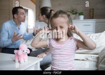 Little girl close ears refuse to hear family fight - Stock Photo