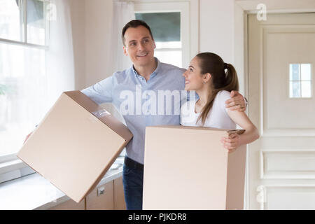 Excited couple holding cardboard boxes entering own house - Stock Photo