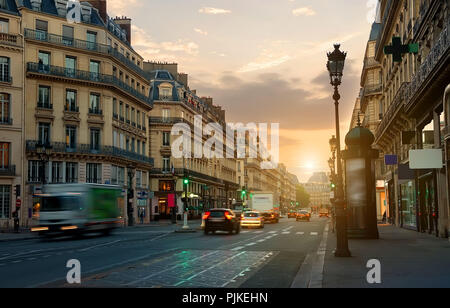 Wide street with road and beautiful architecture in Paris at sunrise, France - Stock Photo