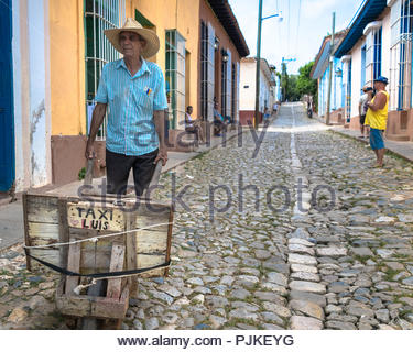 Senior Cuban man pushing a cart in the cobblestone street of the colonial village - Stock Photo