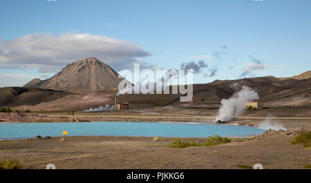 Iceland, Geothermal Power Station, Myvatn area, steaming chimneys, blue lake, volcanic cone in the background - Stock Photo