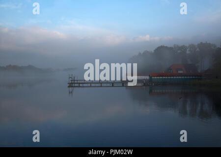 The historic bathhouse on the Great Eutin lake on a foggy autumn morning - Stock Photo