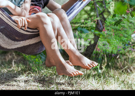 Two girls swinging their legs out of a hammock - Stock Photo