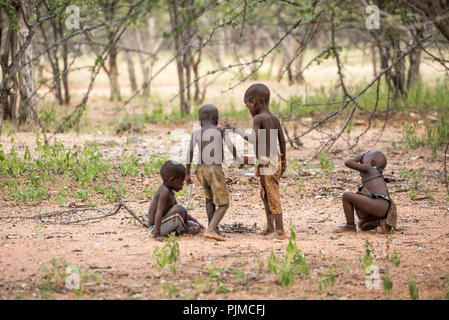 Four Himba children play in the forest, right near the village - Stock Photo