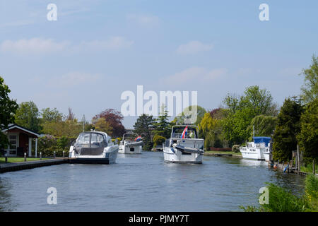pleasure motor sailing yachts on the water between the holiday homes on a summer day in Nederand - Stock Photo