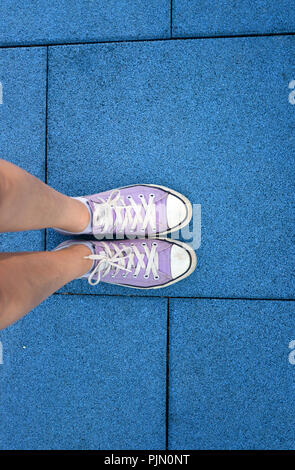 woman, wearing purple canvas shoes, standing on a soft blue tiled fllor in a playgrround - Stock Photo