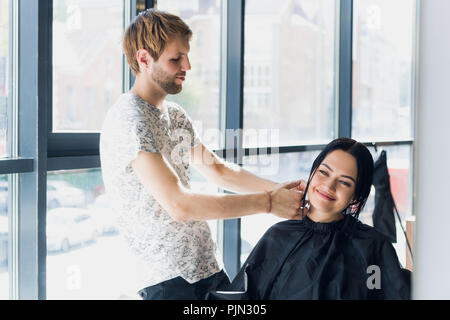 A woman in a hairdressing salon waiting to see the results looking in a mirror, smiling and talking with artist - Stock Photo