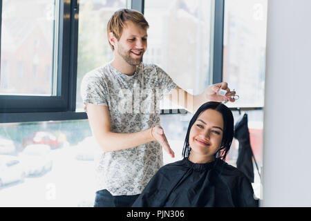 Young woman looking in the mirror after haircut. - Stock Photo