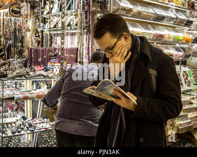 ISTANBUL, TURKEY - DECEMBER 28, 2015: Lost and puzzled tourist reading the istanbul edition of the Tourist Guide Book Lonely planet in Kapalicarsi, th - Stock Photo