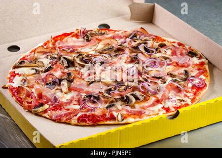 Pizza prosciutto crudo prepared and put in cardboard packaging - Stock Photo