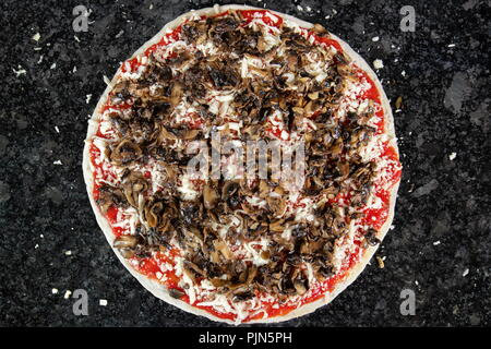 Pizza with mushrooms on black table, ready to be put in the oven to be baked - Stock Photo